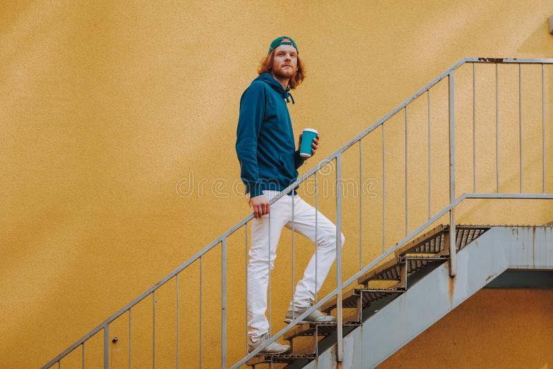 Young hipster man walking on stairs with coffee. Urban lifestyle concept. Full length side on portrait of young red haired hipster guy walking on flight of royalty free stock photos