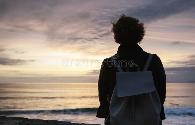 Young hipster relax on the beach on background ocean sunrise, silhouette romantic person looking view evening seascape, girl enjoy. Sunset on coast, travel stock image