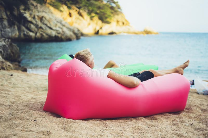 Young hipster relaxing on coastline beach on inflatable lazy air pouffe sofa, person tourist enjoy sunny day on background coast. Sea waves, calm concept mockup royalty free stock images