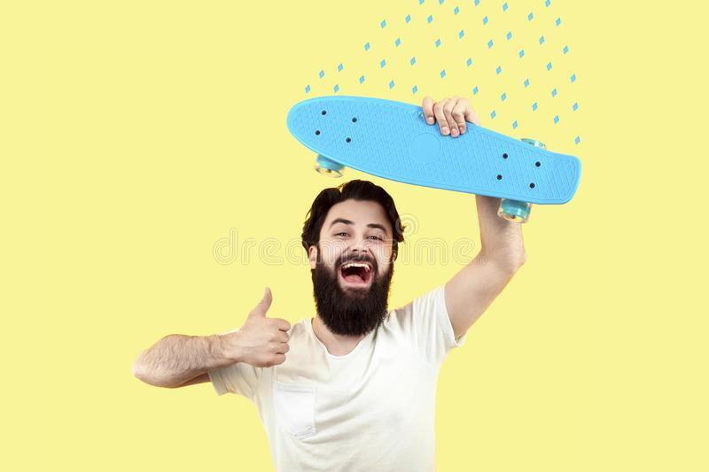 Young hipster with skateboard. Cheerful hipster man holds skateboard and shows like, concept of summer mood, image on a yellow background stock image