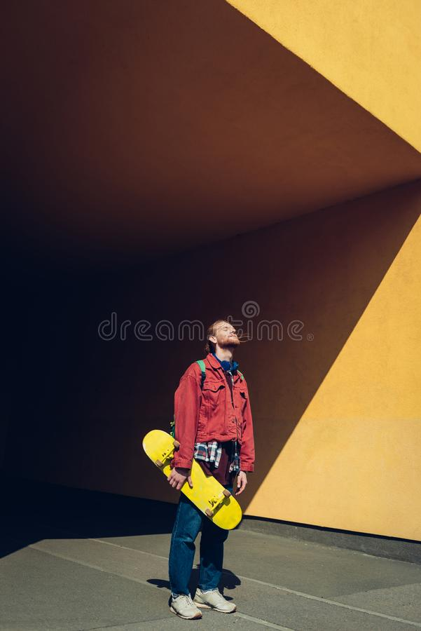 Young hipster skater man enjoying sun light. Urban lifestyle and activity. Full length portrait of smiling young hipster guy with yellow skateboard closing eyes stock image