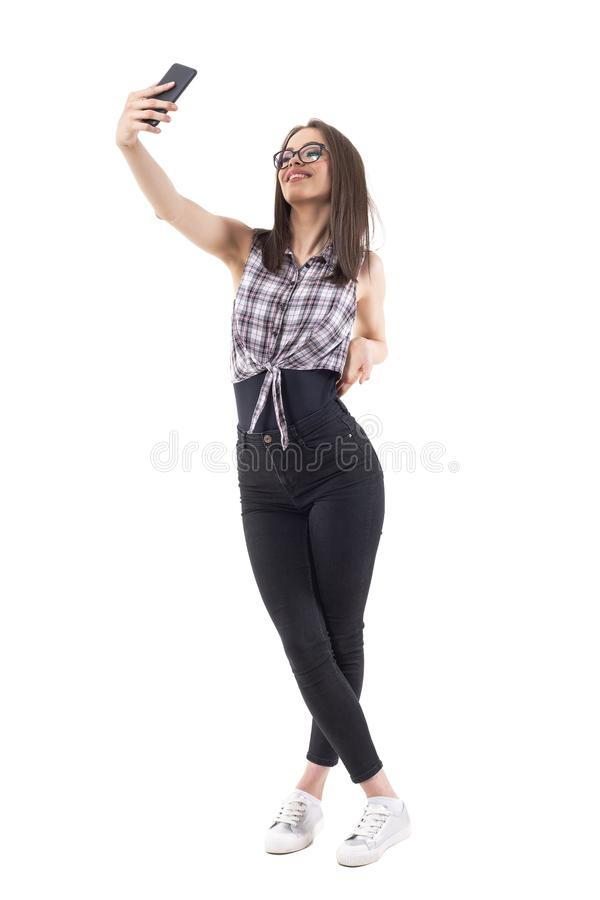 Young hipster style teenage woman taking photo smiling and posing for selfie. Full body isolated on white background royalty free stock images