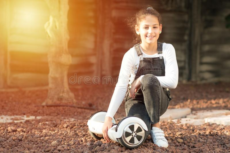 Young hipster teenager girl balancing on electric Hover Board, Dual Wheel Self Balancing Electric Skateboard sunny park. stock photo