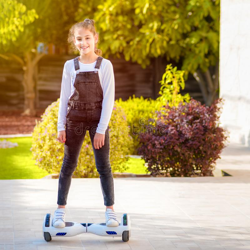 Young hipster teenager girl balancing on electric Hover Board, Dual Wheel Self Balancing Electric Skateboard sunny park. stock image