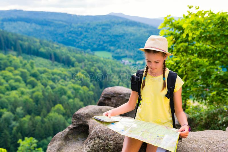 Young hipster tourist girl holding and looking map on trip; life stock photos