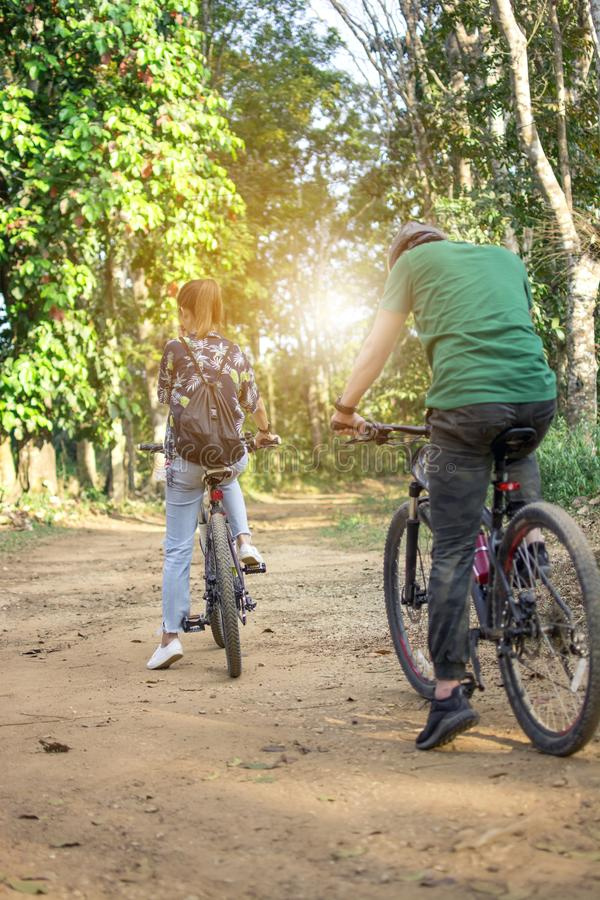 Young Hipster tourist riding bicycles in the forest back to camera, Couple mountain biking to the forest trail, back view. Selective focus royalty free stock photo