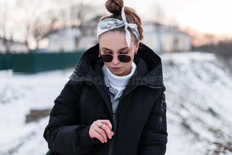 Young hipster woman in black sunglasses in a black winter coat with a stylish leather backpack with a bandana in a white sweater stock photos