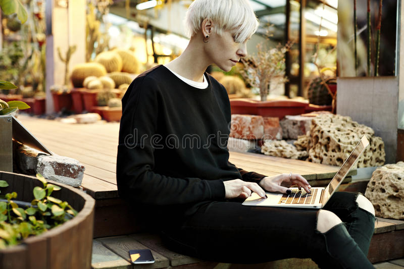Young hipster woman with blonde short hair sitting on stairs, working on laptop stock photos