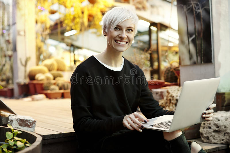 Young hipster woman with blonde short hair smiling and working on laptop, sitting on stairs. Indoor botanical garden interior.  stock photos