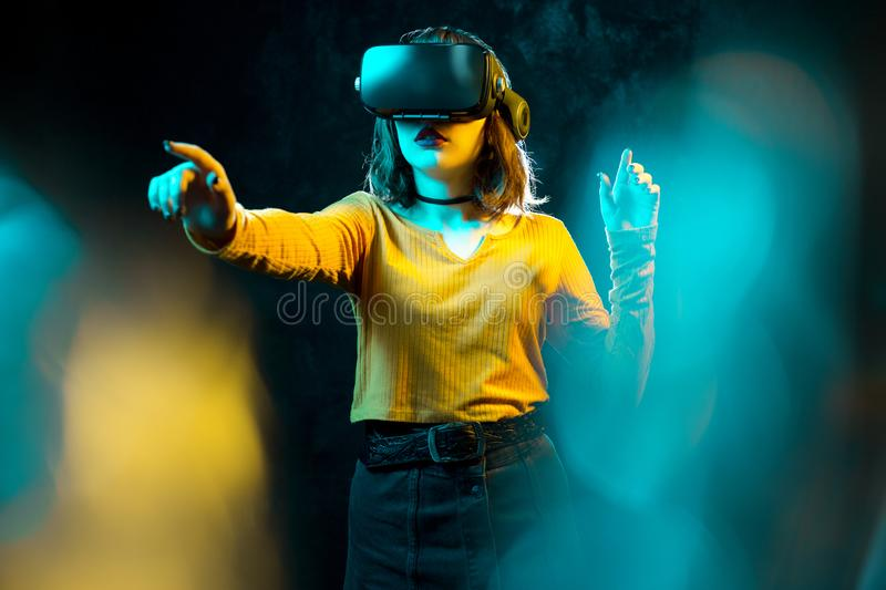Young hipster woman with curly hair wearing virtual reality goggles and touch another world in studio neon lights royalty free stock photos