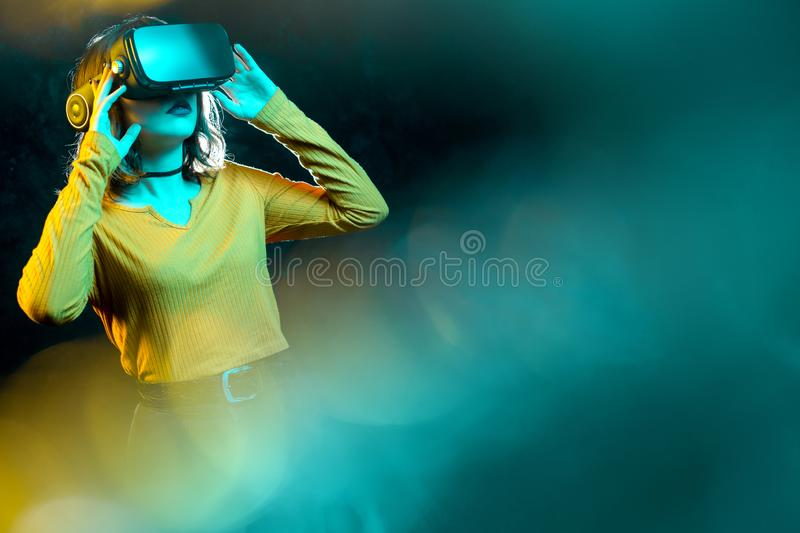 Young hipster woman with curly hair wearing virtual reality goggles and touch another world in studio neon lights royalty free stock photography