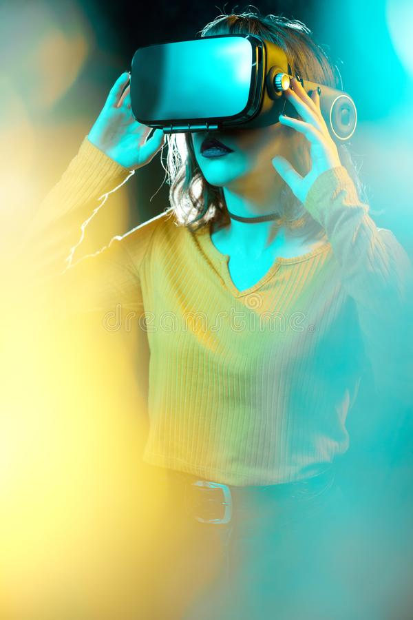 Young hipster woman with curly hair wearing virtual reality goggles and touch another world in studio neon lights royalty free stock image