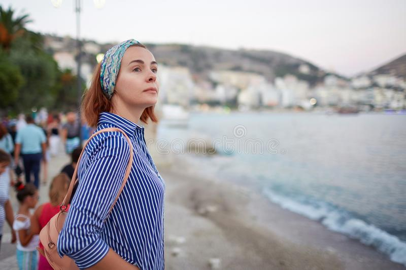 Young hipster woman enjoying sun and good warm day during her recreation time, female looking at the landscape while stock photography