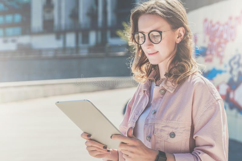Young hipster woman in glasses stands on city street and uses tablet computer.Girl looking on screen of digital tablet. stock image