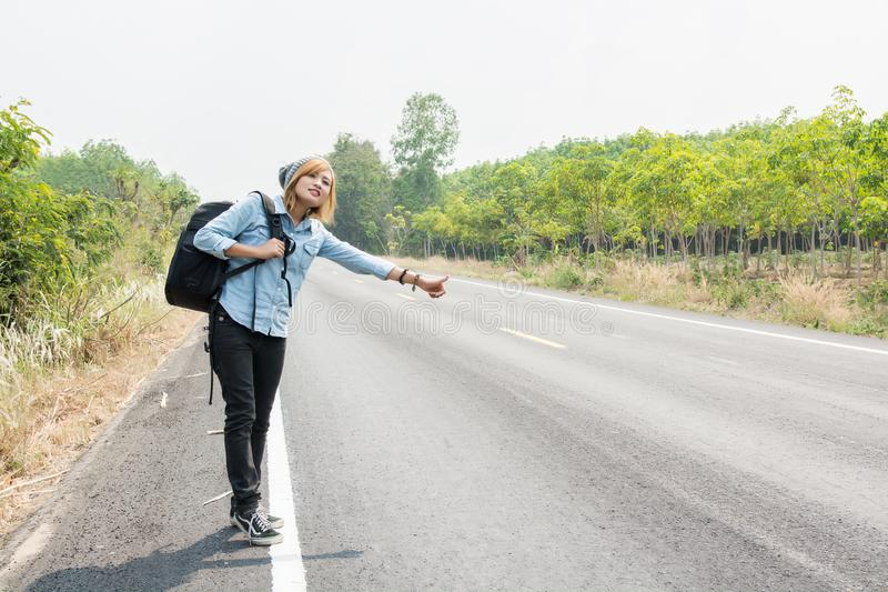 Young hipster woman hitchhiking on countryside road wait for the. Car royalty free stock image