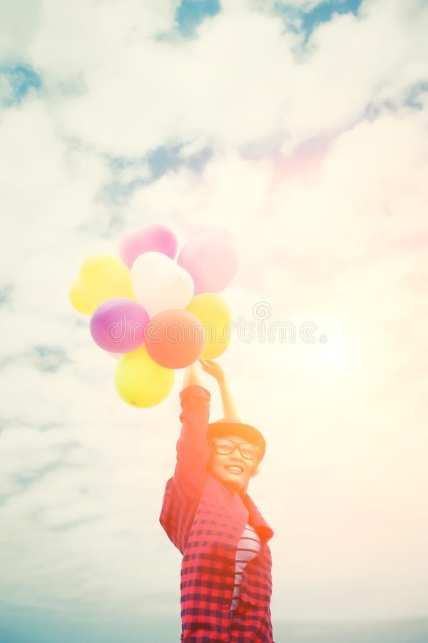 Young hipster woman holding balloons against the blue sky stock images