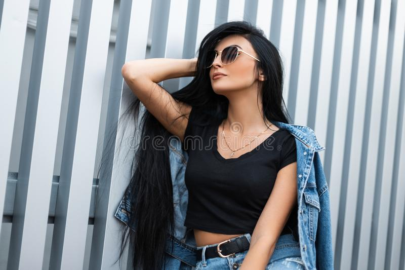 Young hipster woman with luxurious long black hair in a stylish top in a fashionable denim jacket in sunglasses relaxes. In the city near a metal wall. American royalty free stock photos