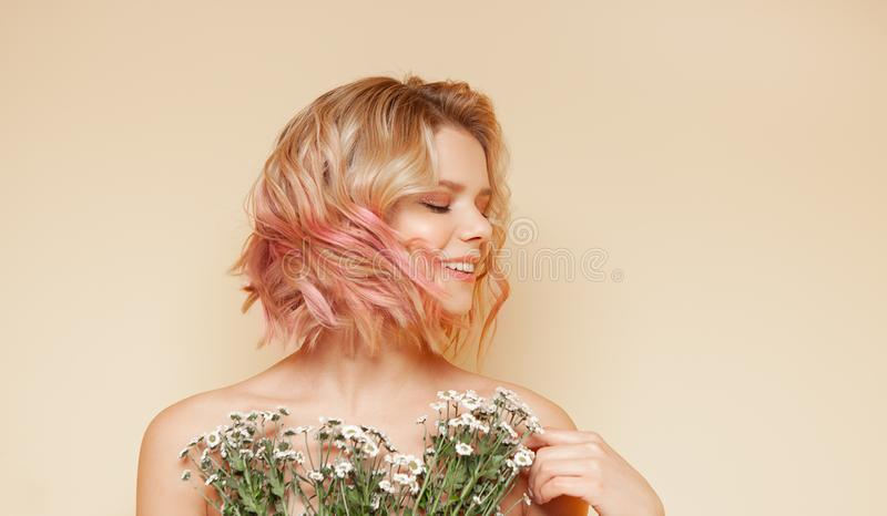 Young hipster woman with pink colored flying curly hairs and wildflowers smiling. On the yellow background royalty free stock photography