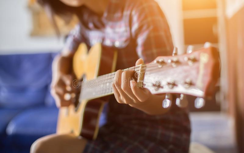 Close up of young hipster woman practiced guitar in the park,happy and enjoy playing guitar stock photos