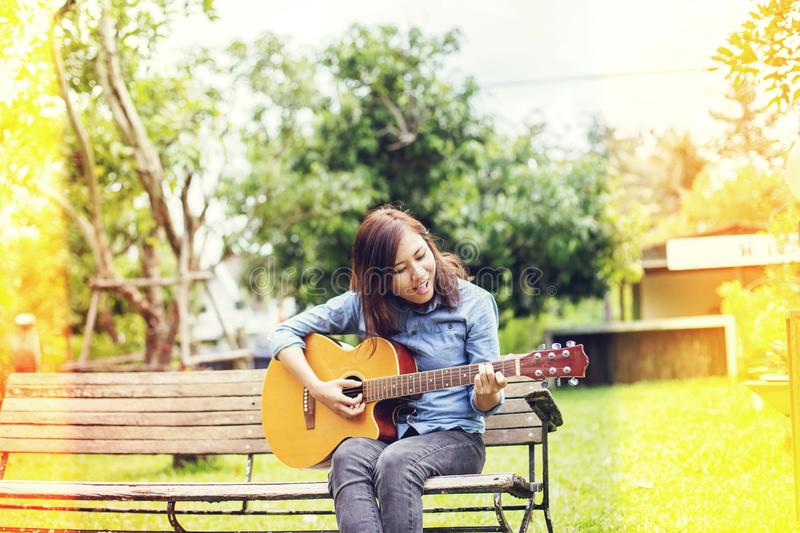 Close up of young hipster woman practiced guitar in the park,happy and enjoy playing guitar stock photography