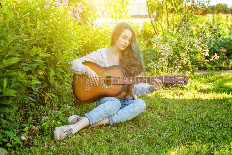 Young hipster woman sitting in grass and playing guitar on park or garden background. Teen girl learning to play song royalty free stock images