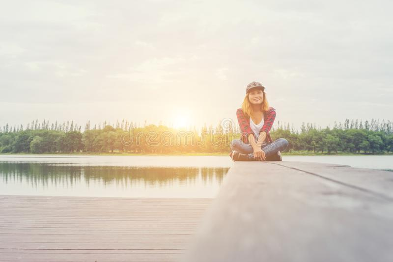 Young hipster woman sitting on pier and smiling at the camera. royalty free stock image