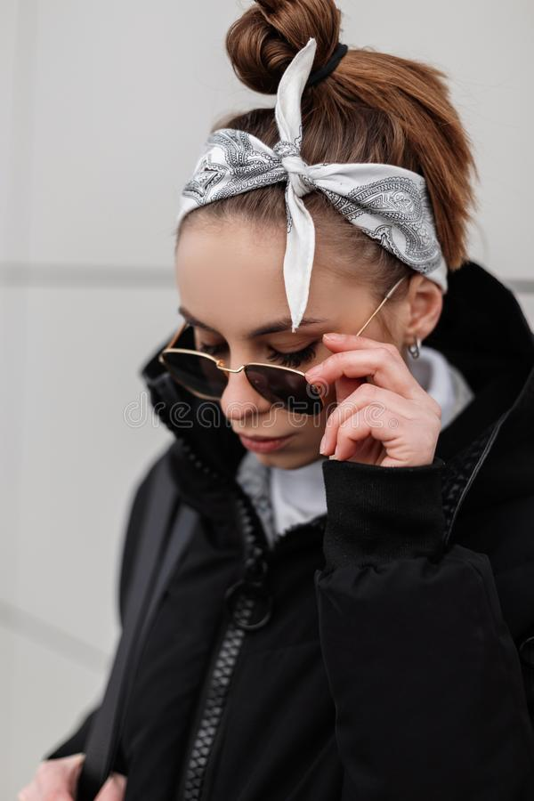 Young hipster woman in trendy sunglasses in a stylish bandana in a winter warm coat posing in a city near a white wall. American fashion girl stock image