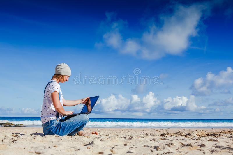 Young hipster woman working on laptop at the beach. On sunny day royalty free stock images