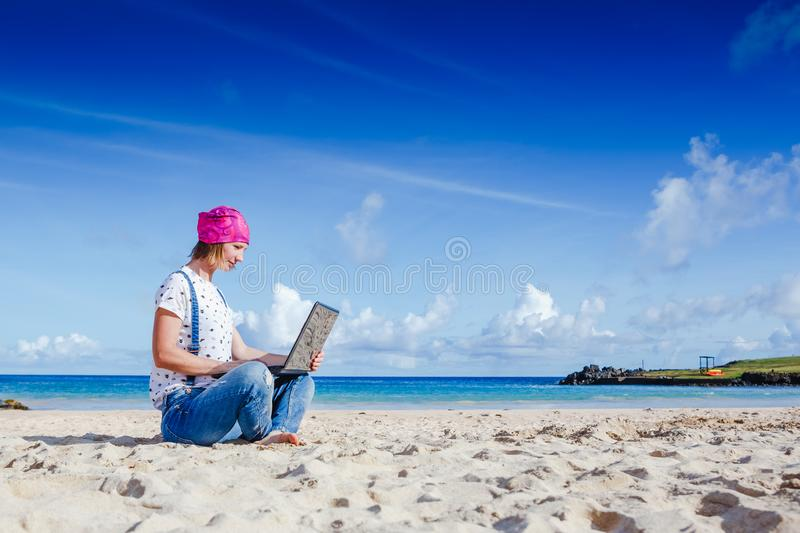 Young hipster woman working on laptop outdoor. Young hipster woman working on laptop at the beach royalty free stock photography