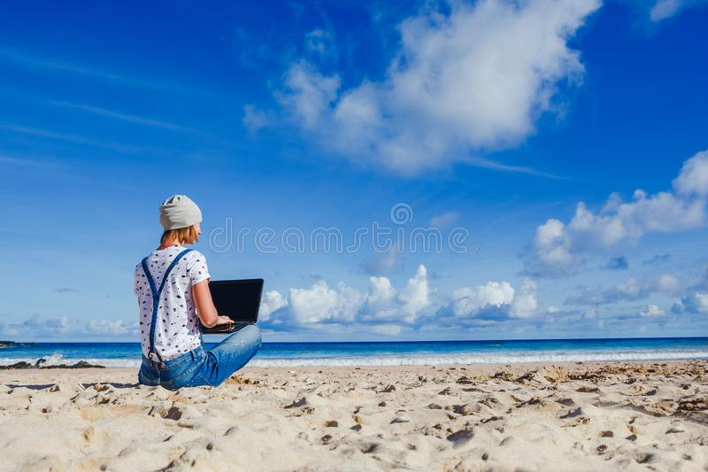 Young hipster woman working outdoor. Young hipster woman working on laptop at the beach stock image