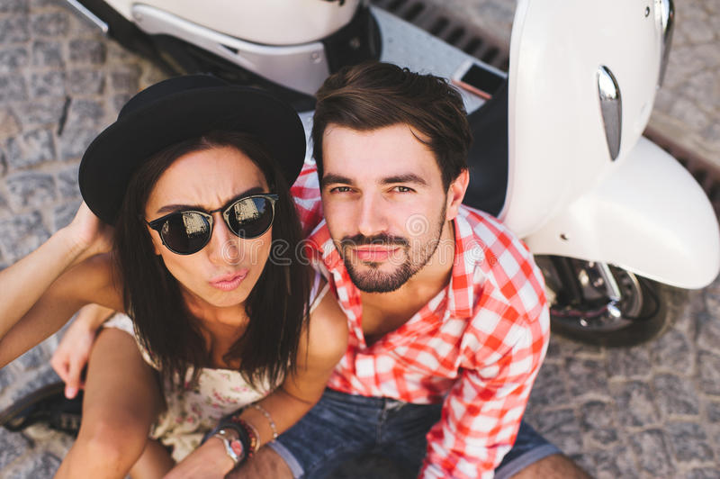 Young hipsters couple in love sitting near a scooter stock image
