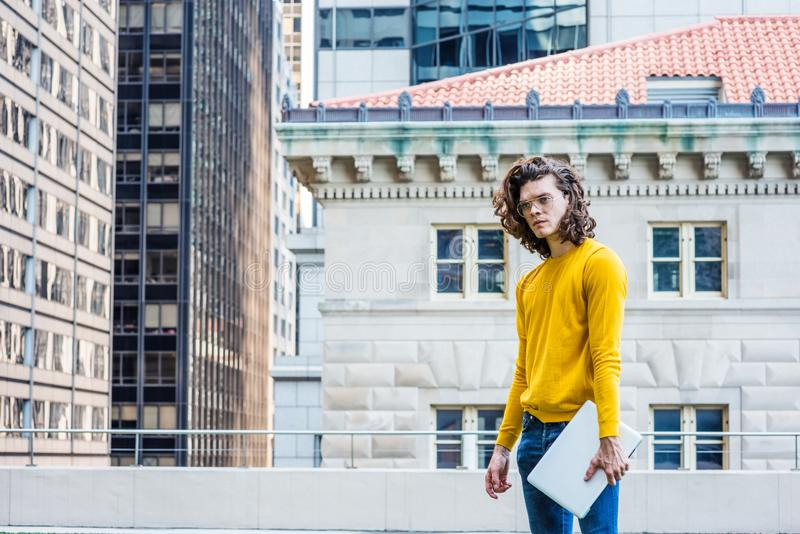 Young Hispanic American College Student Studying in New York Cit. Y, with brown curly hair, wearing glasses, yellow long sleeve T shirt, blue jeans, holding royalty free stock photography