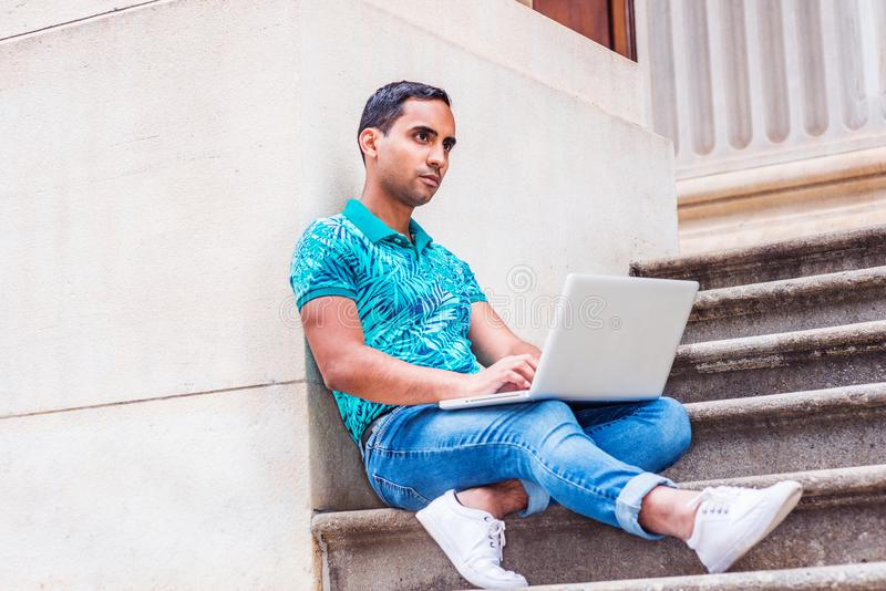Young Hispanic American college student studying in New York. Wearing green patterned Polo shirt, blue jeans, white sneakers, sitting on stairs of office royalty free stock image