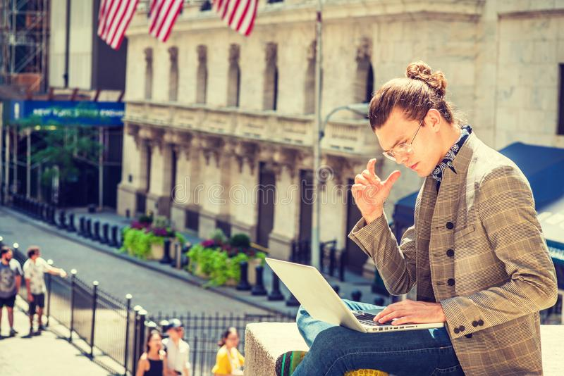 Young Hispanic American Male College Student traveling, studying. In New York City, with hair bun, wearing glasses, brown patterned jacket, blue jeans, sitting stock image
