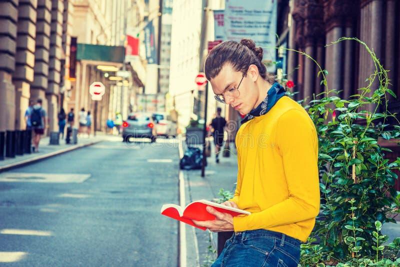 Young Hispanic American Man reading red book on street in New Yo. Young Hispanic American Man with hair bun, wearing glasses, yellow long sleeve T shirt, small royalty free stock photos