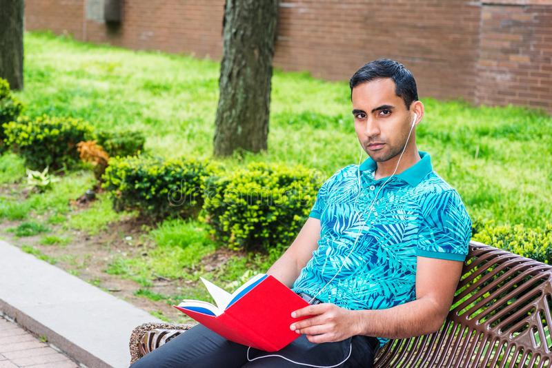 Young Hispanic American Man reading red book outside in New York. Young Hispanic American Man wearing green patterned Polo shirt, black pants, white wired royalty free stock photo