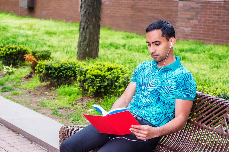 Young Hispanic American Man reading red book outside in New York. Young Hispanic American Man wearing green patterned Polo shirt, black pants, white wired royalty free stock photos