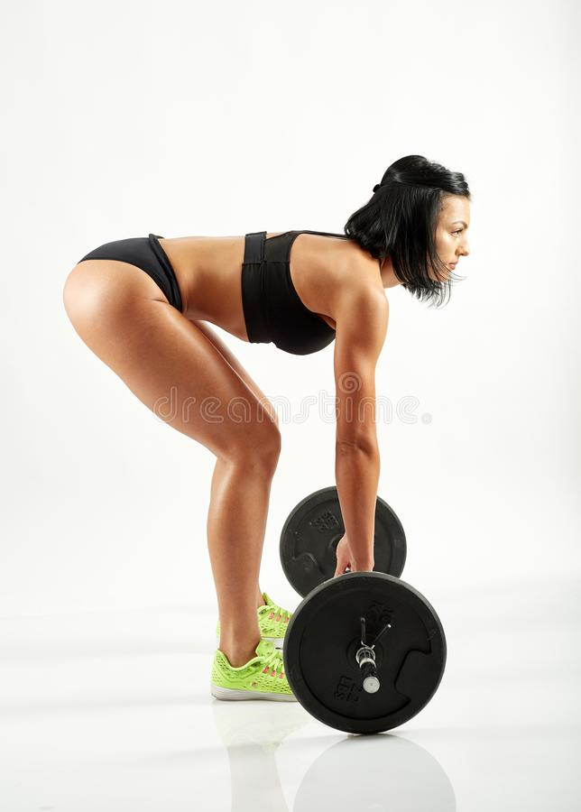 Young woman doing deadlift with barbell stock photos