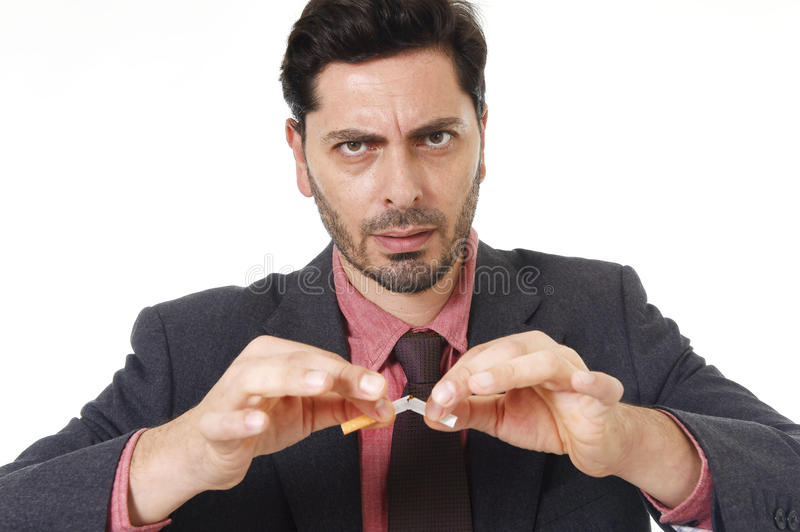 Young hispanic attractive man breaking cigarette in quit smoking resolution royalty free stock images