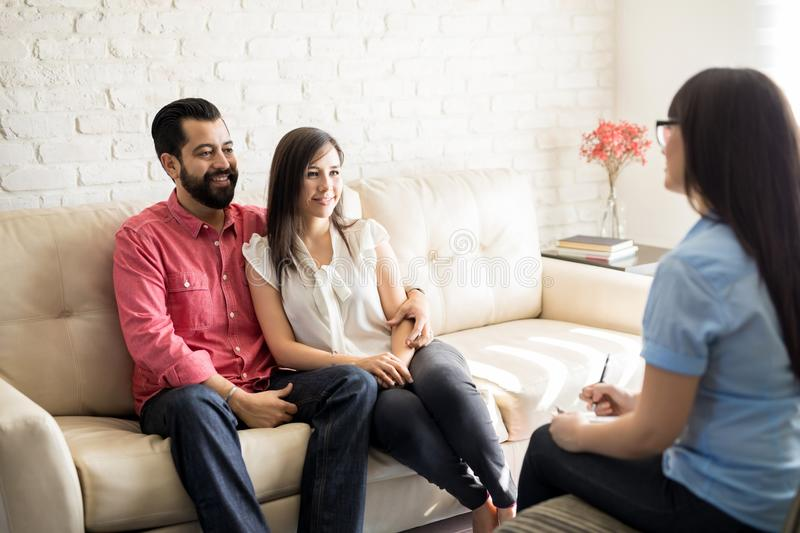 Young Hispanic couple during psychotherapy session. Loving hispanic couple sitting on couch during psychotherapy session royalty free stock images