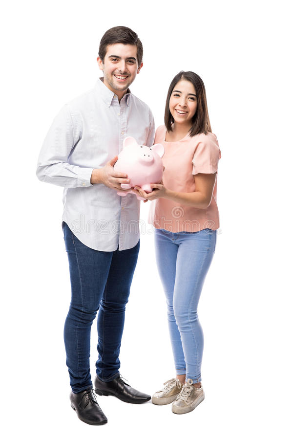 Young Hispanic couple saving some money. Attractive young Hispanic couple saving some money in a piggy bank and smiling in a white background royalty free stock image