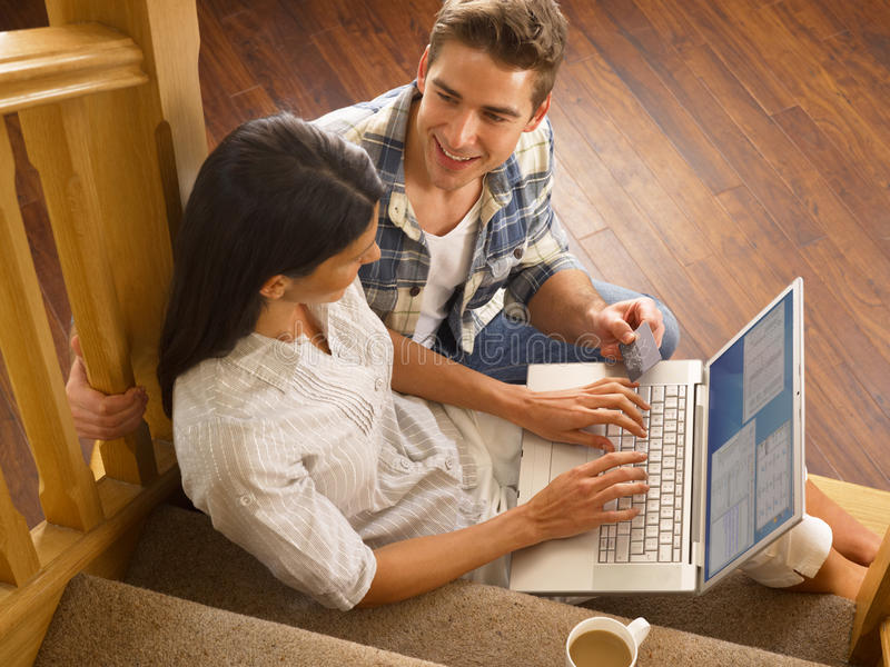 Young Hispanic couple shopping online. At home royalty free stock image