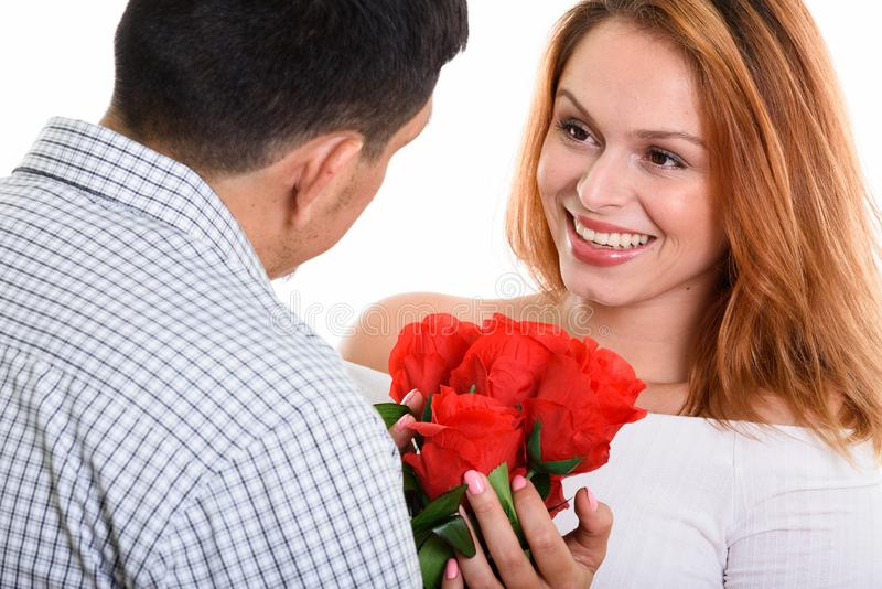 Young Hispanic couple together in love man proposing for marriage. Young happy couple smiling and in love with happy women holding red roses stock photos