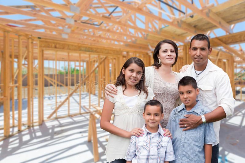 Young Hispanic Family On Site Inside New Home Construction Framing. stock images