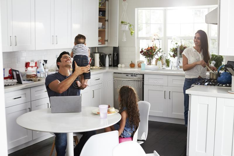 Young Hispanic family in their kitchen, dad holding baby in the air, mum cooking at the hob stock photos