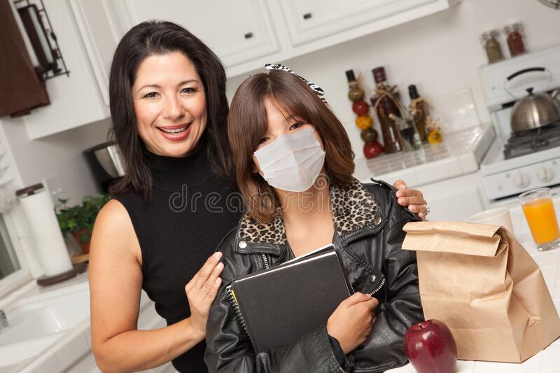 Young Hispanic Girl Student with Mother At Home Getting Ready For School Wearing Medical Face Mask stock photos