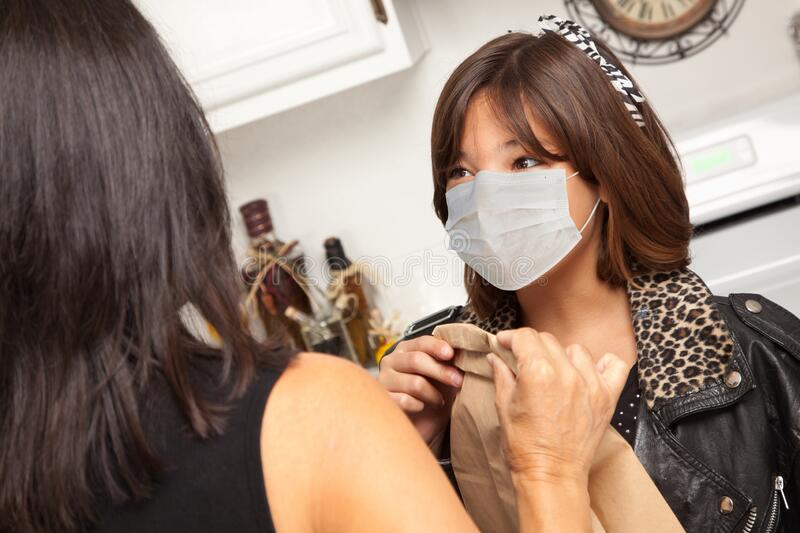 Young Hispanic Girl Student with Mother At Home Getting Ready For School Wearing Medical Face Mask royalty free stock photography