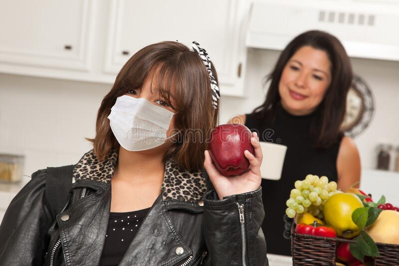 Young Hispanic Girl Student with Mother At Home Getting Ready For School Wearing Medical Face Mask royalty free stock images
