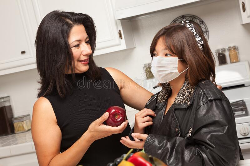 Young Hispanic Girl Student with Mother At Home Getting Ready For School Wearing Medical Face Mask stock photography