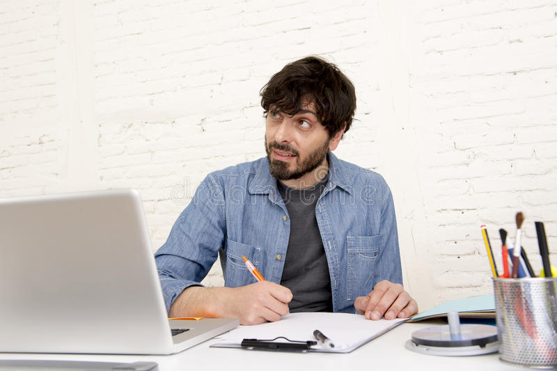 Young hispanic hipster businessman working at computer home office. Corporate portrait of young hispanic attractive hipster businessman on his 30s working at stock images